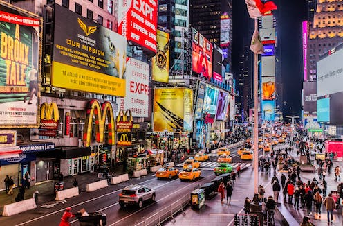 Time Square is lit up with lots of digital billboards.