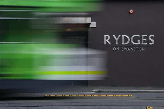 Blurred outline of a tram passing the Rydges hotel.