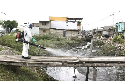 Man in protective suit sprays disinfectant over a makeshift bridge across a sewage flow in a settlement in Ecuador.