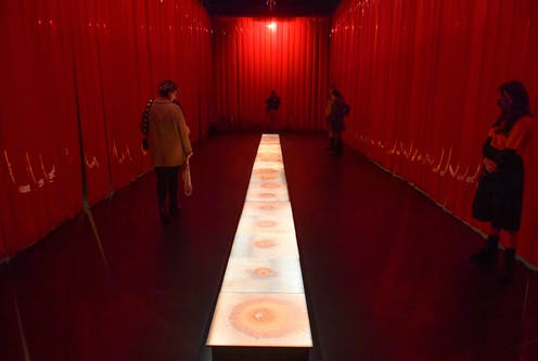 Red curtain around a floor projection with people exploring the space.