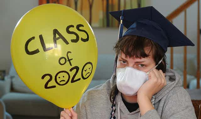 """Depressed student with graduation hat and mask sitting at home holding balloon with """"class of 2020"""" written on it."""