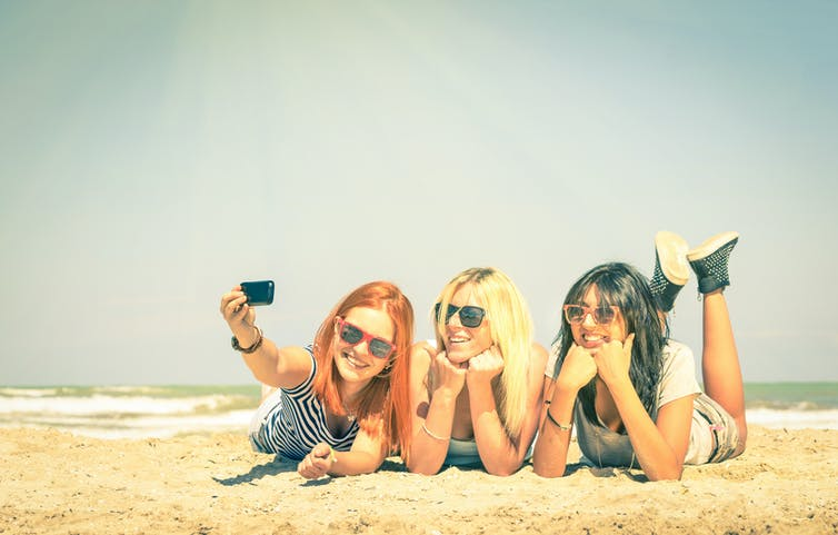 Three girls lying on towels on the beach and taking a selfie.