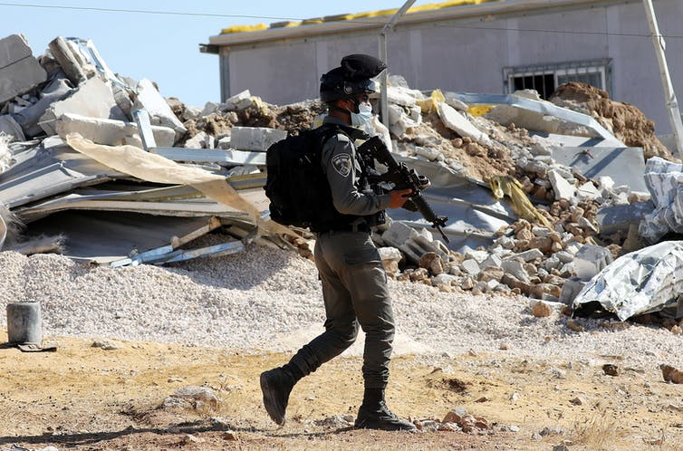 An Israeli border police officer outside a house being demolished in the West Bank.