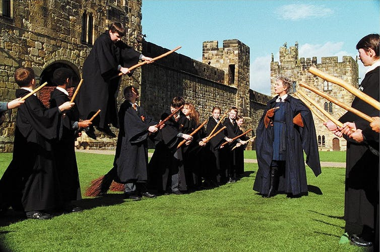 Young people dressed in black robes attempt to ride broomsticks in Harry Potter film.