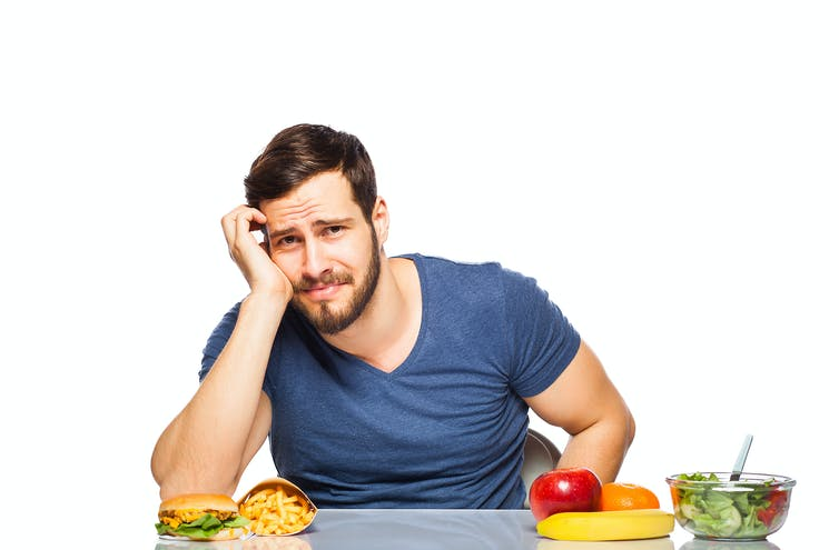 Man deciding between healthy and unhealthy food.