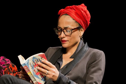 Zadie Smith in a red turban adn black suit reads from her book NW.