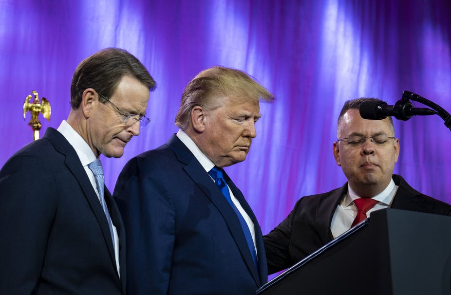 Three men including Donald Trump praying in front of a lectern.