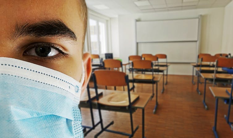 The left side of a man's masked face on the right in the foreground, with an empty classroom in the background.