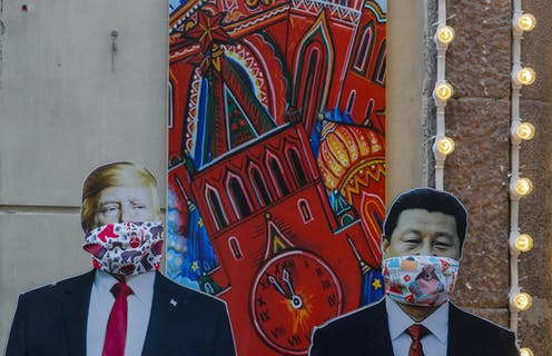 Life-size images of Donald Trump and Xi Jinping with face coverings
