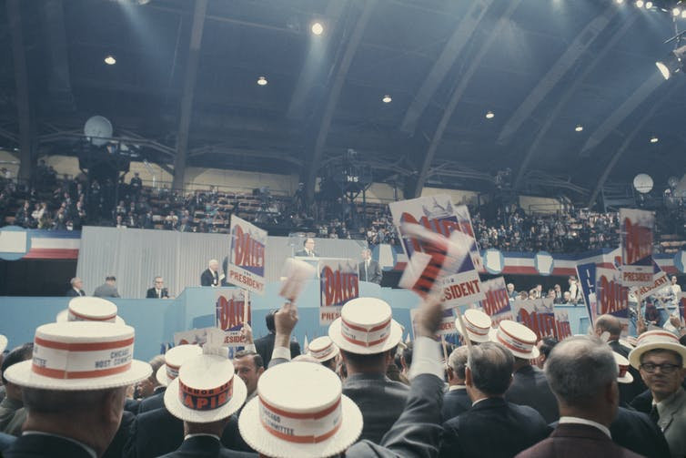 A crowd of people in straw hats wave signs at a stage.