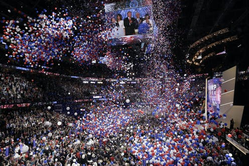 Massive numbers of balloons fall from a convention center ceiling over a crowd of people.