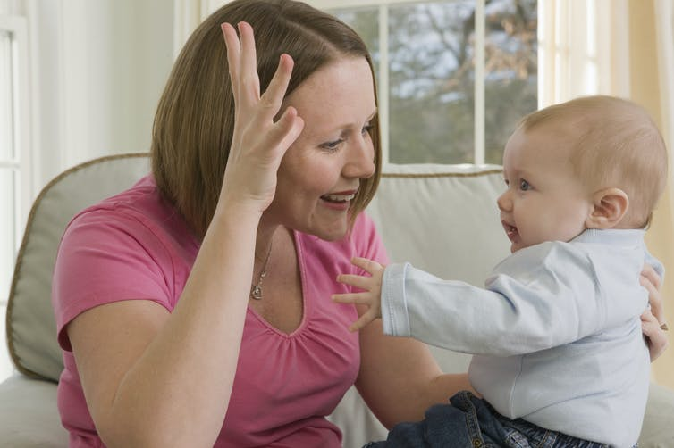 A white mother signing to her attentive baby who is mimicking the hand gesture