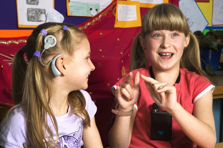 A twelve year old girl dressed in a red top and an nine year old girl dressed in a lilac top communicate with sign language. The younger girl is fitted with a cochlear implant and the older girl wears a voice amplifier.