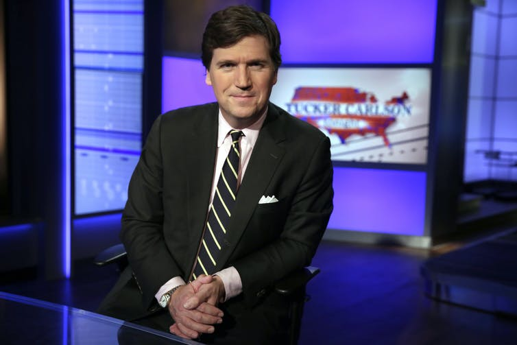 A portrait of Fox News host Tucker Carlson posing on the set of this TV show
