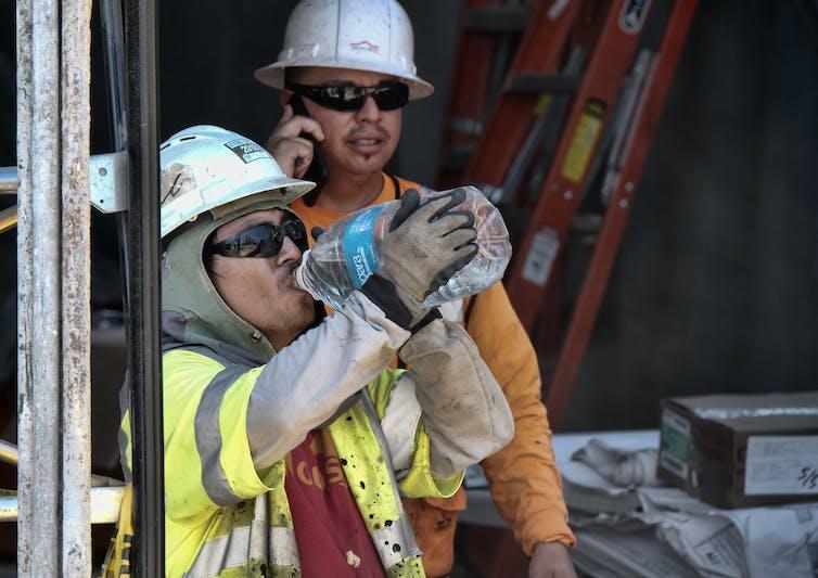 Construction worker drinking water in heat