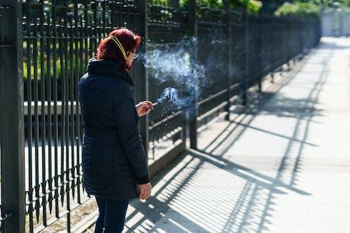Una mujer fuma junto a la reja de un parque en Granada.