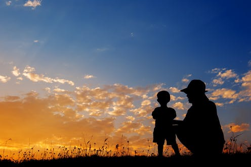 Silhouette of mother playing with small son.