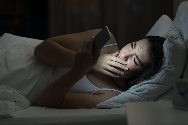 Young woman in bed at night using mobile phone.