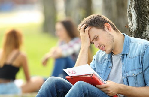 University student stares in dismay at his failed assignment