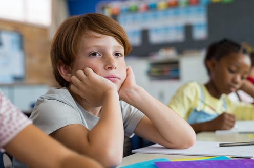 Boy looking sad or thoughtful sitting in class with chin in his hands.