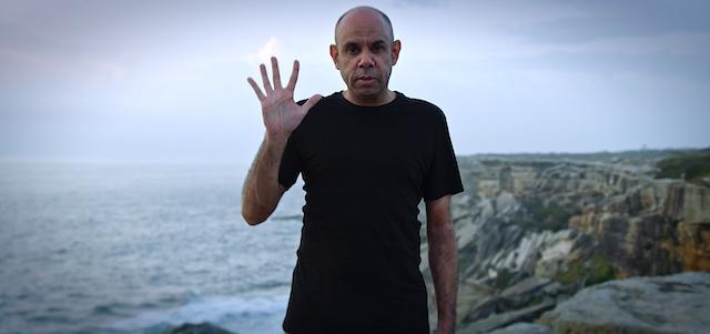 Man waves at camera in coastal location