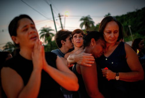 Women mourn after a dam collapse in Brazil.