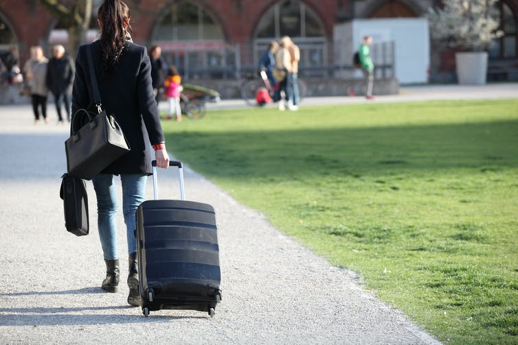 Young woman walking with suitcase