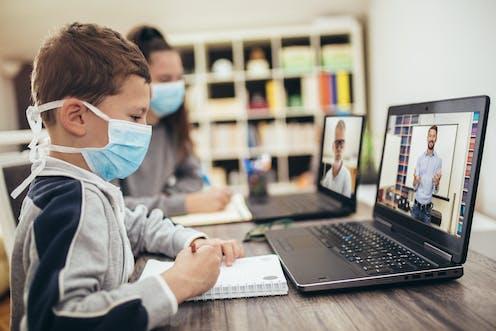 Niños con mascarilla, ante un cuaderno y un ordenador en el que se ve al profesor.