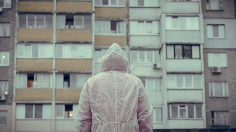 Una persona con un buzo blando, de espaldas, ante un edificio de viviendas.