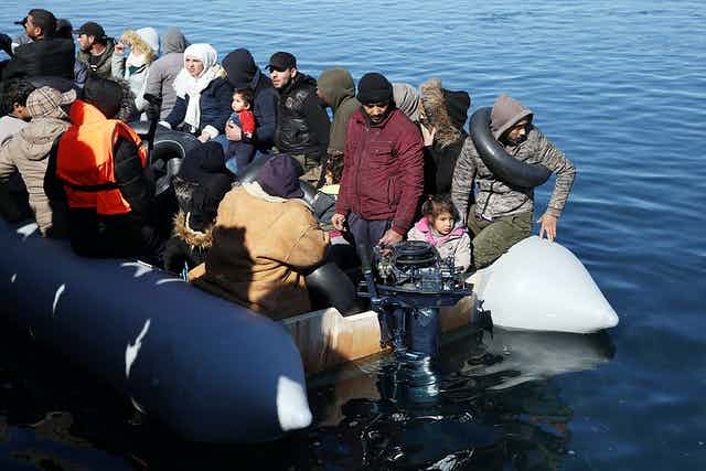 Refugees in an overcrowded dinghy low in the water