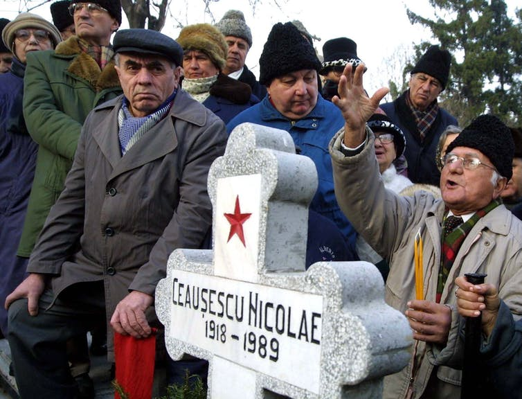 People surround the grave of the late Romanian dictator Nicolae Ceaușescu at Bucharest's Ghencea cemetery.