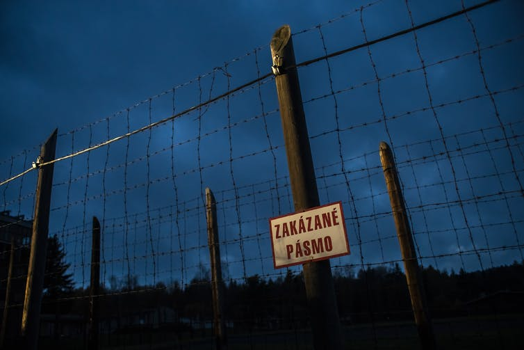 Fence at Vojna labour camp in Czech Republic with sign in Czech.
