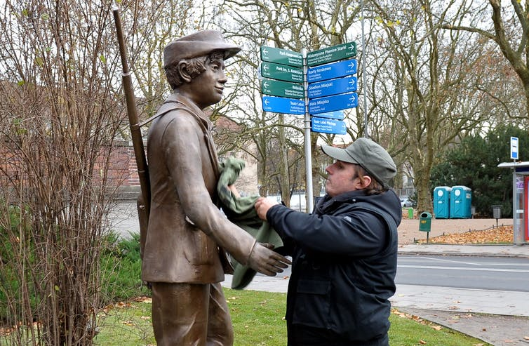 A man installing a statue of a young resistance fighter at Statue Park in Budapest, Hungary.