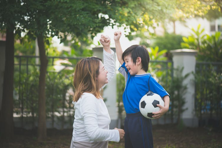 A mother crouches before her young son who holds a soccer ball.