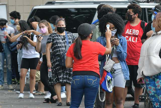 A line of students and parents waits to have their temperature taken before entering Hollywood High School.
