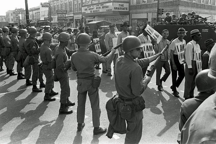 A photo from 1968 showing striking sanitation workers marching past Tennessee National Guard troops with bayonets in Memphis, Tenn.