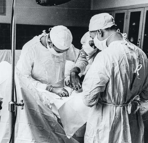 Three doctors hunched over a patient performing surgery, faces covered by surgical masks.
