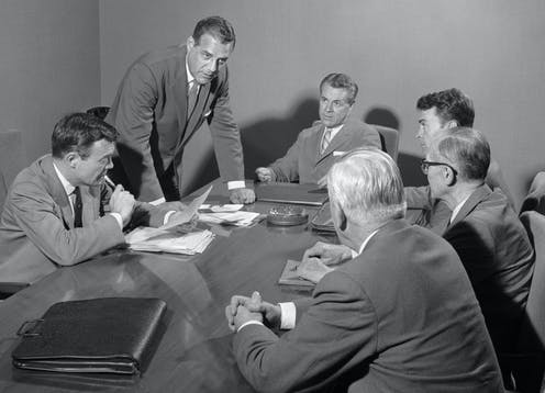six white men in suits around a 1950s boardroom table