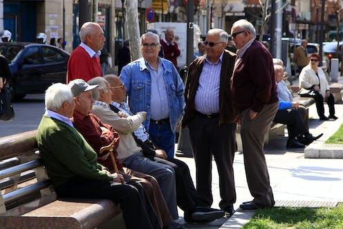 Ocho señores mayores en un banco de una plaza de Madrid.