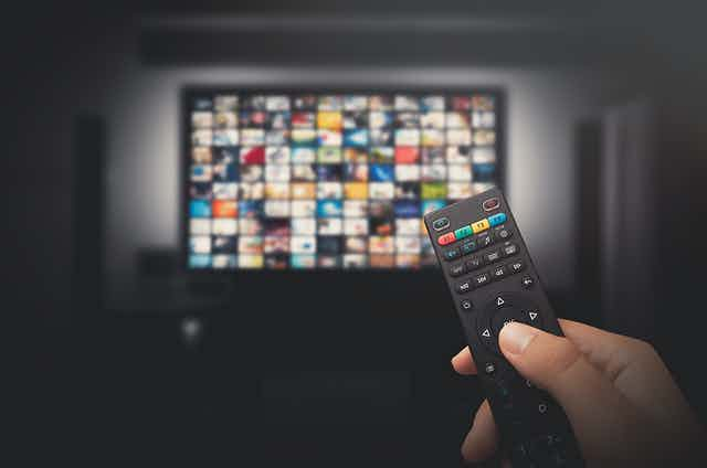 A tv with video thumbnails in the background and a hand holding a remote in the foreground