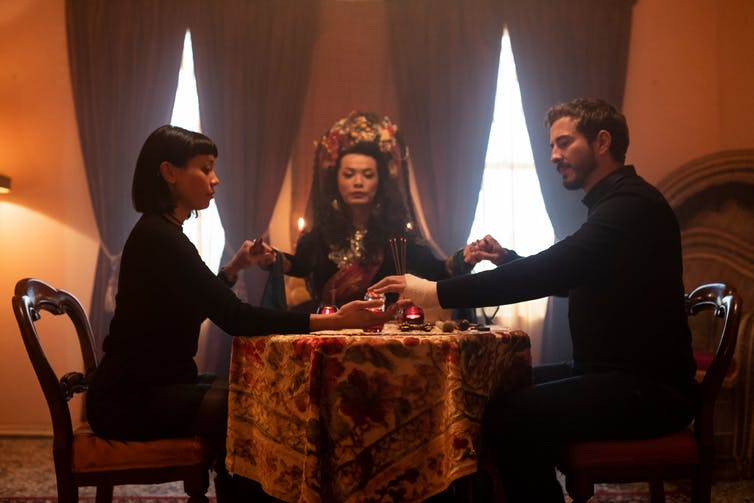 Movie still of a seance table.