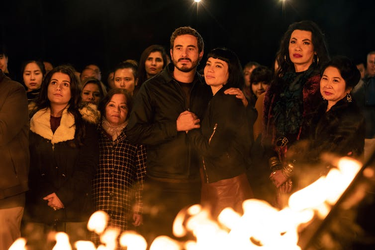 Movie still, people gathered around a bonfire.