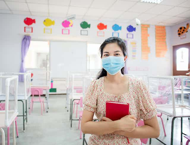 A woman wearing a blue face mask sits in an empty children's classroom, holding a red book.