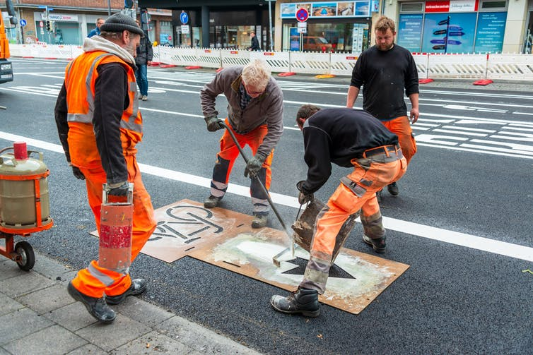 Road workers apply a bicycle symbol on the road