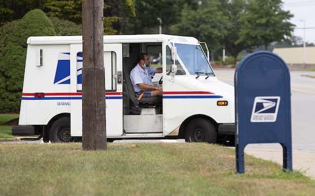 A US postal service worker in van alongside mailbox