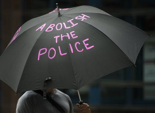 """a photograph of someone holding a black umbrella with the words """"abolish the police"""" in pink letters"""