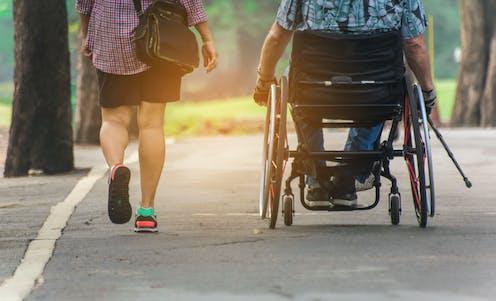 Dos personas de espaldas, una de ellas en silla de ruedas, pasean por un parque.