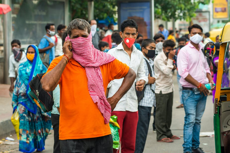 Migrant workers in India stand in the street wearing face masks.