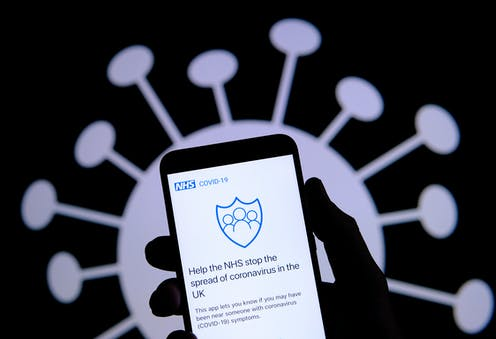 Hand holding smartphone displaying contact tracing app with virus image in background