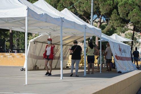 Tienda de campaña de la Cruz Roja en un parque de Sabadell y gente haciéndose pruebas PCR